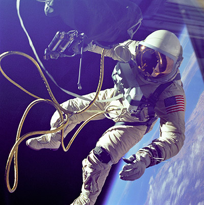On June 3, 1965 Edward H. White II became the first American to step outside his spacecraft and let go, effectively setting himself adrift in the zero gravity of space. For 23 minutes White floated and maneuvered himself around the Gemini spacecraft while logging 6500 miles during his orbital stroll. White was attached to the spacecraft by a 25 foot umbilical line and a 23-ft. tether line, both wrapped in gold tape to form one cord. In his right hand White carries a Hand Held Self Maneuvering Unit (HHSMU) which is used to move about the weightless environment of space. The visor of his helmet is gold plated to protect him from the unfiltered rays of the sun.